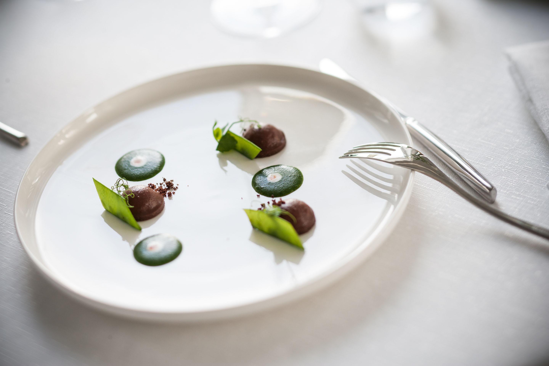 BOTTONI DI OLIVA TAGGIASCA Vellutata di ortica, aglio di Vessalico, punta di Tabasco, tartare di pescato, bacello di piselli, glassa di oliva Taggiasca.